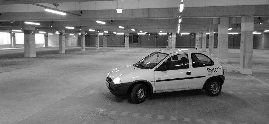 Bild von einem weißen Kleinwagen in einer Tiefgarage, das Auto trägt die Aufschrift ByteFM
