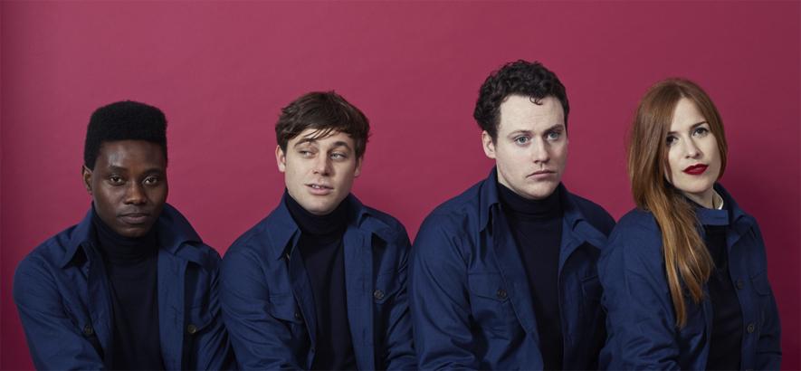 Foto der britischen Band Metronomy – es zeigt drei Männer und eine Frau in blauen Hemden vor einem violetten Hintergund
