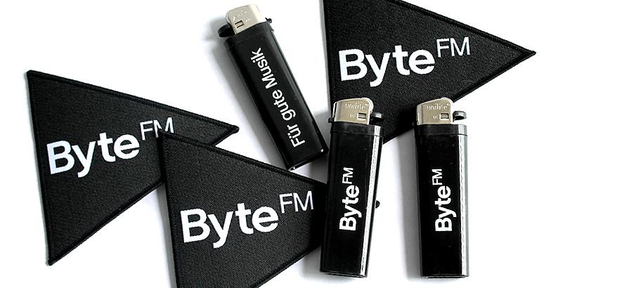 Foto eines Feuerzeugs mit ByteFM Logo und eines Aufnähers mit ByteFM Logo
