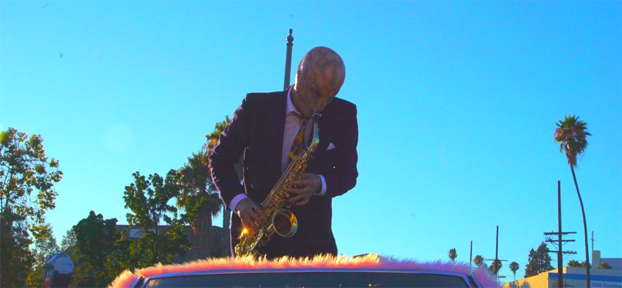 """Ein Echsenmensch spielt Saxofon auf einem mit Kunstfell überzogenen Sportwagen. Szene aus """"Sonali"""", dem neuen, von Mac DeMarco gedrehten Musikvideo von Iggy Pop."""