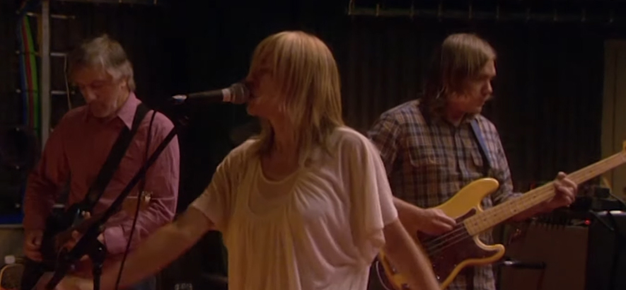 "Film-Still aus der Sonic-Youth-Performance für ""From The Basement"" mit Lee Ranaldo an der Gitarre, Mark Ibold am Bass und Kim Gordon am Mikrofon."