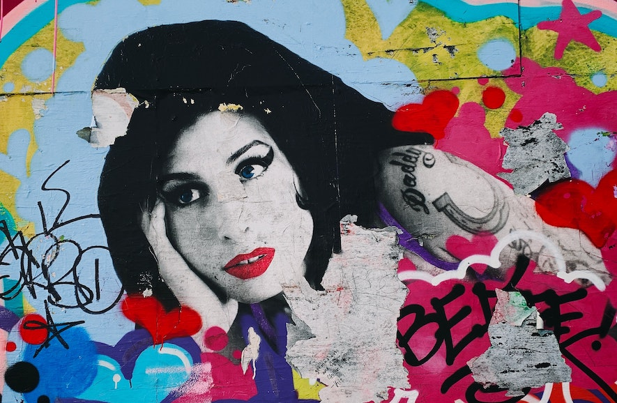 Buntes Grafitti von Amy Winehouse an einer Mauer.