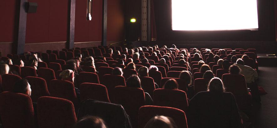 Foto eines Kinosaals mit Besucher*innen, die auf die erleuchtete Leinwand schauen