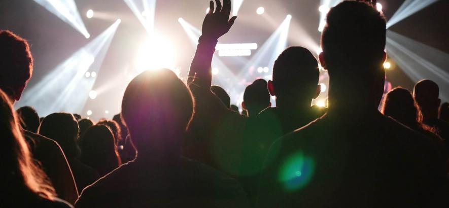 Foto von Menschen in der Rückansicht, die in einem Club stehen und auf die hellerleuchtete Bühne schauen