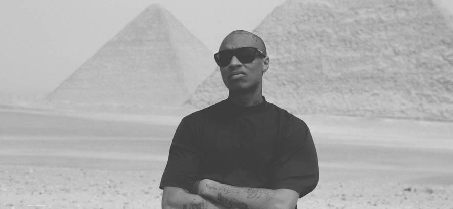 """Schwarz-Weiß-Pressebild des Rappers Rejjie Snow, der mit Tinashe& Grouptherapy unseren Track des Tages """"Disco Pantz"""" aufgenommen hat."""